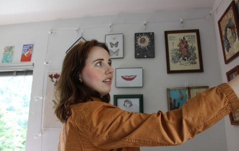 Gianna Fransisco, adjusting her eclectic collection of art work and photos that adorn the walls around her bed.   Heidi Speck | The Falcon