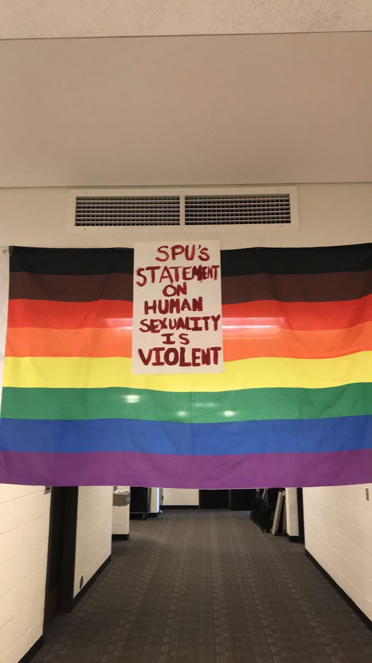 Signs made by students were hung in the hallway and on the walls, surrounding the protesters.   Ben Hansen | The Falcon