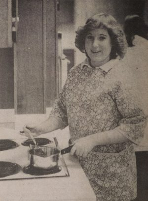 a woman stands behind a stove cooking