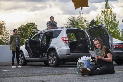 A woman sits in a parking lot and opens birthday presents