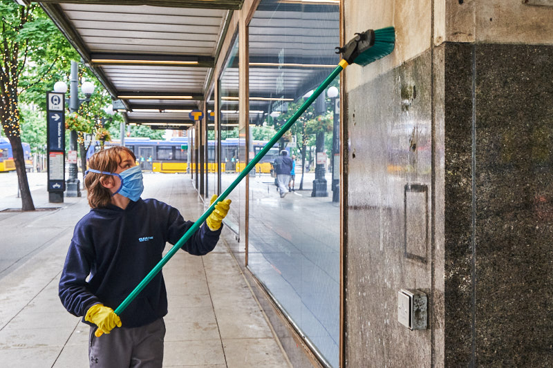a boy cleans graffiti off of a wall