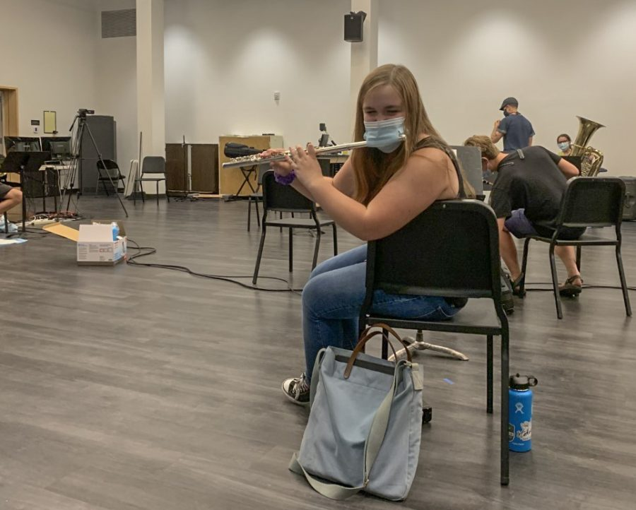 Cora Bruders, in Nickerson Studios, demonstrating how she plays the flute through an altered mask.