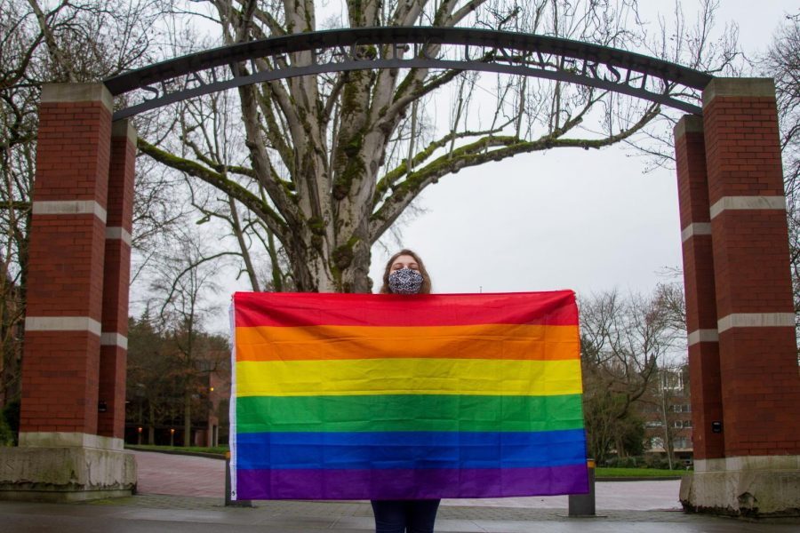 Laurelae Bluntzer holds her flag up with pride in front of the school's arch. She had attended the recent protest against SPU's anti-LGBTQIA+ hiring policies.